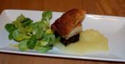 Belly pork bite with black pudding, crispy crackling, apple sauce and salad garnish
