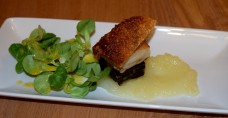 Belly pork bite with black pudding, crispy crackling, apple sauce and salad garnish