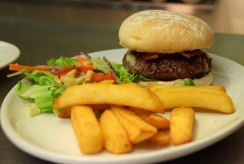 Homemade burger with local rare breed beef in a toasted bun with mayonnaise, cheddar cheese, smokey relish and crispy bacon served with chunky chips and salad