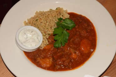 Richly spiced tagine of local lamb and apricots on giant couscous topped with minted yoghurt